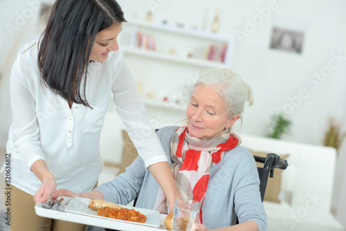 woman serving meal to injured woman Canvas Print