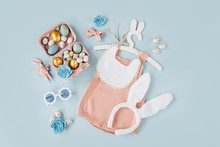 Cute Baby Costume Easter Bunny. Knitted Bodysuit With Fluffy  Bunny Ears, Easter Eggs And Candy On Blue Background. Holiday Concept. Flat Lay, Top View
