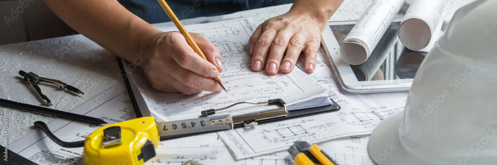 Fototapeta Architects concept, engineer architect designer freelance work on start-up project drawing, construction plan. architect design working drawing sketch plans blueprints and making construction model