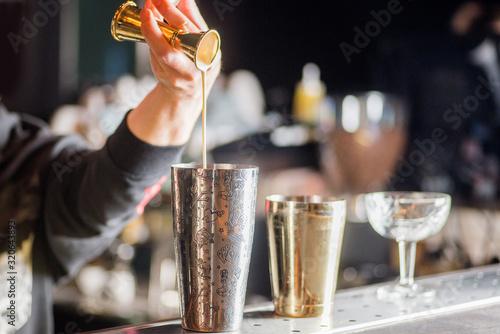 Fotografia bartender is preparing a cocktail. Bartender pours a cocktail