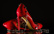 Patent Leather Shiny Female Red Stilettos And Beads On A Black Background