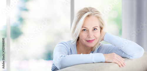 Obraz Beautiful business woman smiling friendly and looking in camera near the window in office. Happy woman's face closeup. Selective focus. - fototapety do salonu