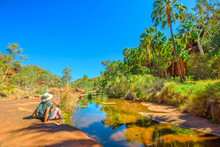Tourist Woman Relaxing After Trekking Along Arankaia Walk In The Heart Of Palm Valley Oasis Waterhole, Finke Gorge National Park, Outback, Northern Territory, Central Australia