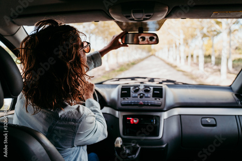 Fotografie, Obraz young beautiful woman driving a van by a path of trees