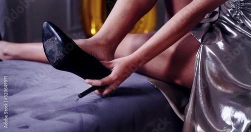 Une femme enlève sa chaussure à talon Canvas Print