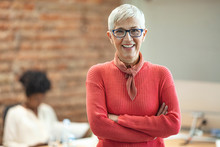 Close-up Portrait Of Mature Business Woman Standing At Office. Pretty Older Business Woman, Successful Confidence With Arms Crossed In Financial Building. Mature Female In Office With Team