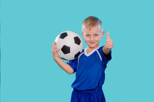 Happy Little Kid In Sportswear Holding A Soccer Ball Isolated On Blue Background