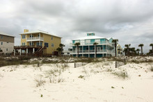 Travel America And Visit Alabama Background.Cloudy Seascape With Freshly Built After Hurricane Colorful Houses For Vacation Rentals And White Sand In A Foreground. Alabama Gulf Shores Beach Area, USA.