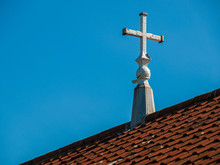 White Cross On Rooftop Against Clear Blue Sky