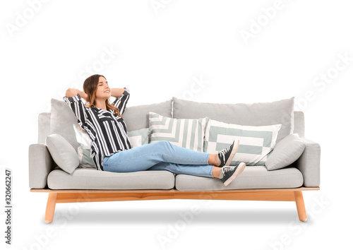 Cuadros en Lienzo Young woman relaxing on sofa against white background
