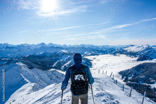 backpacker walking on the ridge at the summit of the snow covered mountain Fototapet