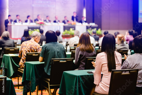 Obraz na plátně Selective focus to business woman sitting with blurry chairman of the meeting and executive committee background in auditorium for shareholders meeting or seminar event, Annual shareholder meeting