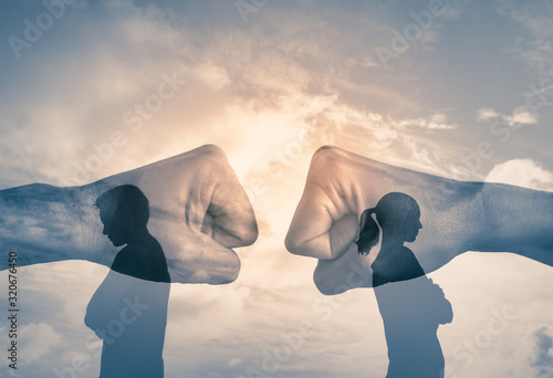 Photo Couple with back turned away from each other with fist clashing in the background
