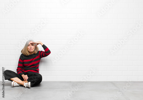 Photo senior or middle age pretty woman looking bewildered and astonished, with hand o