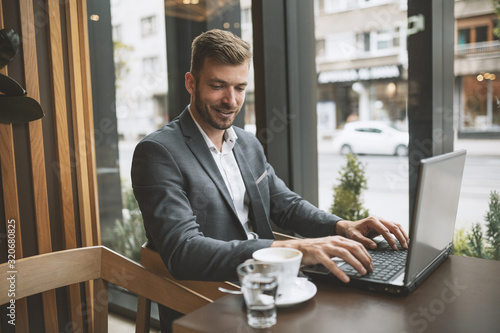 Fototapeta Business manager drinking coffee and using laptop obraz