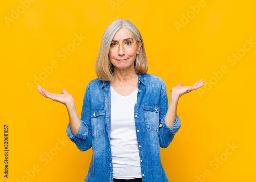 Photo senior or middle age pretty woman feeling puzzled and confused, doubting, weight