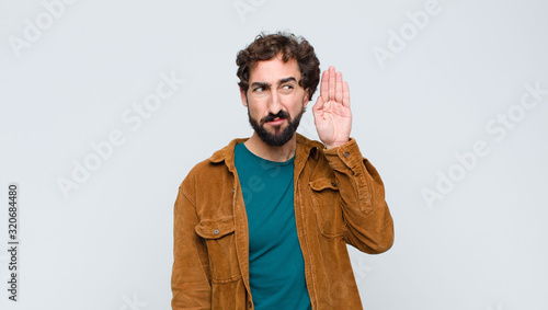 Fotomural young handsome man looking serious and curious, listening, trying to hear a secr