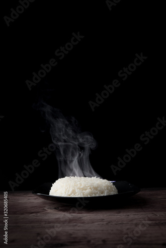 obraz PCV White steam rice with smoke on plate over dark background