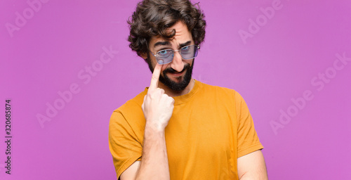 Photo young crazy cool man keeping an eye on you, not trusting, watching and staying a