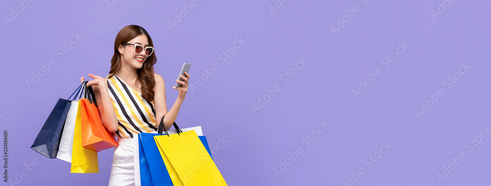 Fototapeta Beautiful Asian woman shopping online with mobile phone on banner background