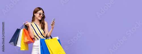 Fototapeta Beautiful Asian woman shopping online with mobile phone on banner background obraz
