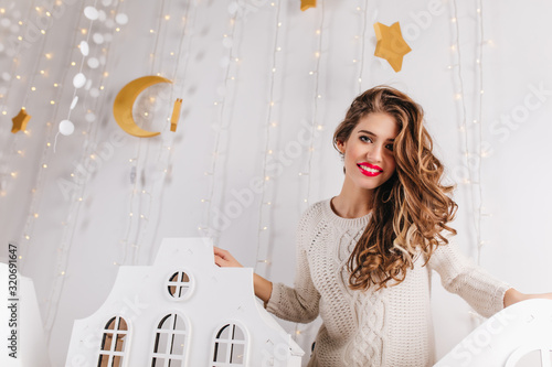 Fotografie, Obraz Cute, attractive girl in warm knitted sweater posing in beautiful decorated bright studio