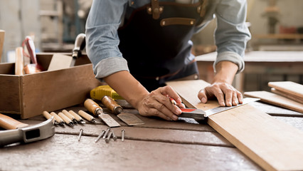 Carpenter working with equipment on wooden table in carpentry shop. woman works in a carpentry shop.