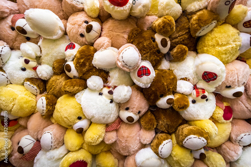 A large pile of teddy bears toys as a background.