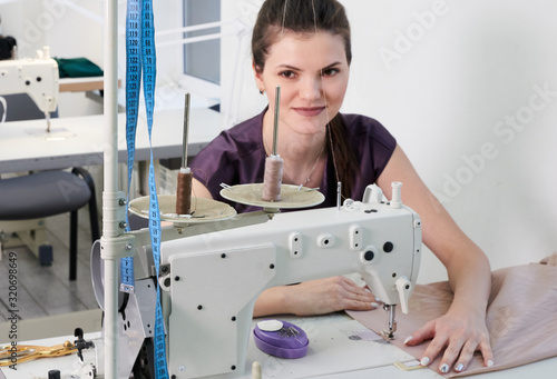 Young tailors sew clothes on sewing machine in atelier studio Wallpaper Mural