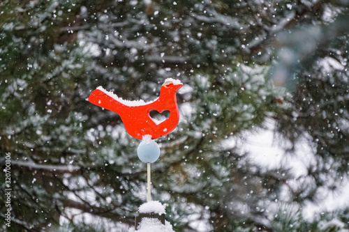 Photo Snow accumulation on red bird cutout with heart during snowstorm