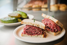 Pastrami Sandwich With A Side Of Pickles Being Served At A Jewish Deli