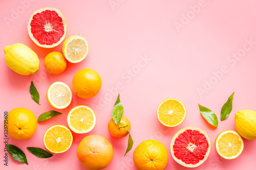 Fresh citrus frame. Oranges, tangerines, grapefruits, leaves on pink background top-down copy space
