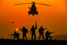 Silhouette Of Military Rangers And Helicopter With Soldier On The Top Of Mountain At Sunset