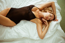 Beautiful Sexy Slim Girl With A Perfect Figure Lies On A White Sheet In Black Bodysuit