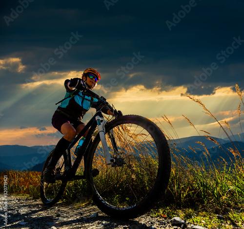 Foto Mountain biking woman riding on bike in summer mountains forest landscape
