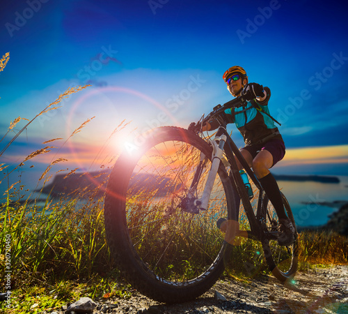 Obraz Cycling woman and man riding on bikes in Dolomites mountains andscape. Couple cycling MTB enduro trail track. Outdoor sport activity. - fototapety do salonu