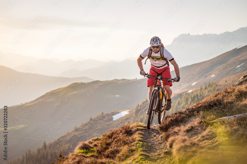 Fototapeta Male mountainbiker riding on a trail in the mountains