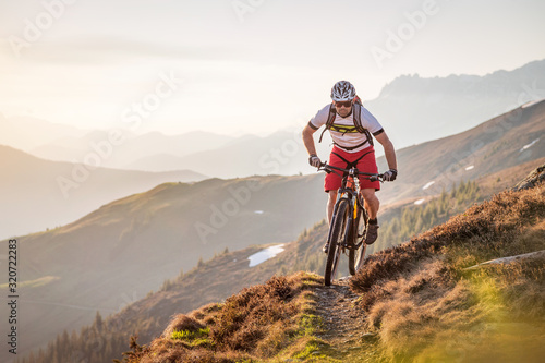 Fototapeta Male mountainbiker riding on a trail in the mountains obraz