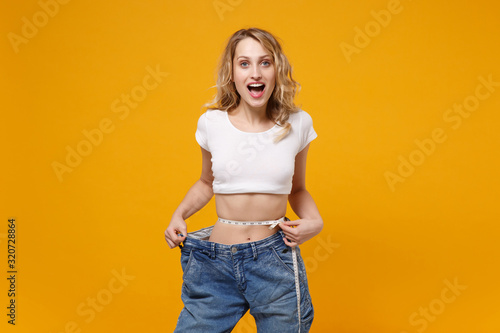 Fototapeta Excited young woman in white t-shirt isolated on yellow orange background. Proper nutrition losing weight healthy lifestyle dieting concept. Wearing old big jeans measuring waist with measure tape. obraz