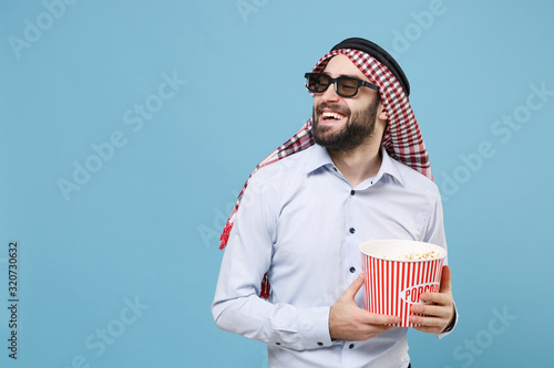 фотография Smiling bearded young arabian muslim man in keffiyeh kafiya ring igal agal 3d imax glasses isolated on pastel blue background