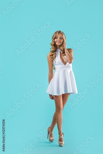 Beautiful young curly blonde woman in white dress posing on blue background Slika na platnu