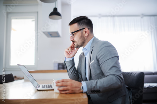 Side view of handsome unshaven caucasian businessman in suit and with eyeglasses looking at laptop and holding mug with fresh morning coffee while sitting at dining table at home.