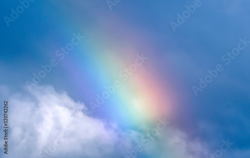 rainbow in blue sky and white cloud © yvonne