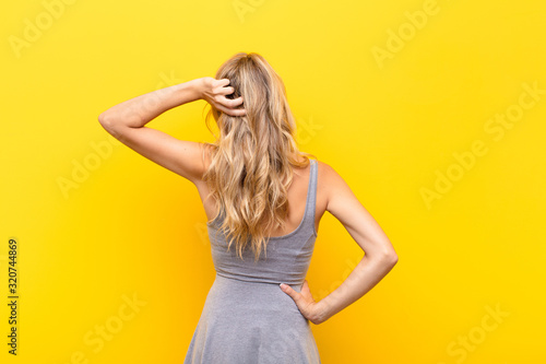Photo young blonde woman thinking or doubting, scratching head, feeling puzzled and co