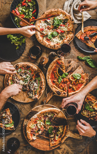 Friends having pizza party dinner. Flat-lay of people eating different kinds of Italian pizza, salad and drinking red wine over wooden table, top view. Fast food lunch, gathering, celebration