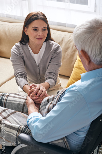 Fototapeta Pretty young brunette female holding hands of aged disable man sitting in wheelchair comforting him during conversation obraz
