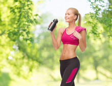 Fitness, Spot And People Concept - Happy Smiling Sporty Woman Drinking Water From Bottle Over Green Natural Background