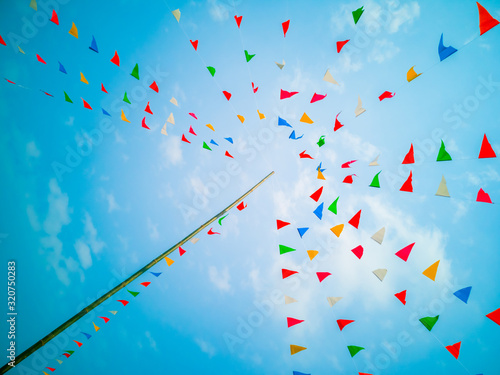 Obraz Colorful flags, colorful party decorations, small triangular flags to celebrate the party with the blue sky and clouds as the holiday concept background. - fototapety do salonu