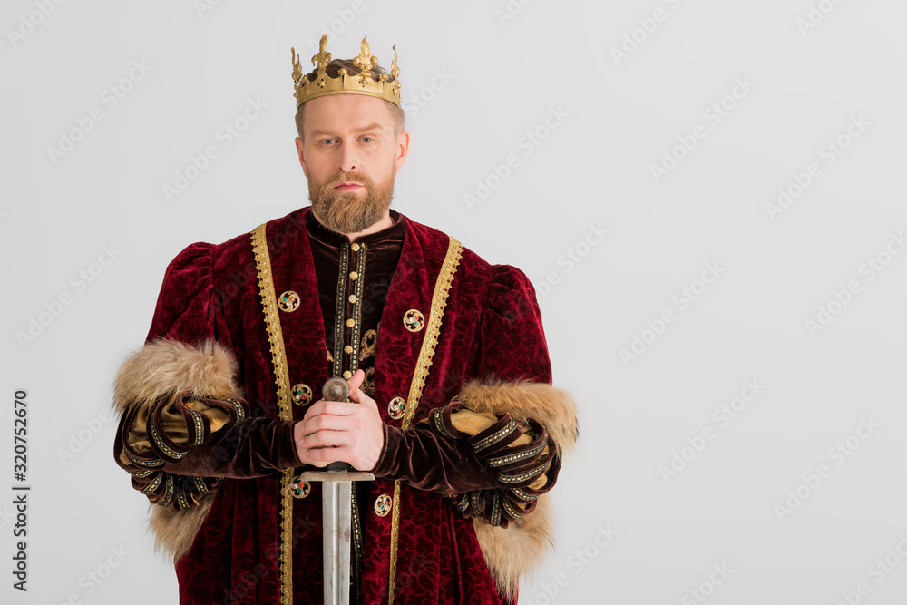 Fototapeta serious king with crown holding sword isolated on grey