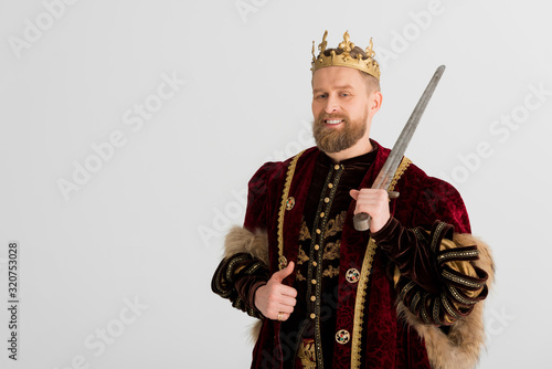 Cuadros en Lienzo smiling king with crown holding sword and showing like isolated on grey